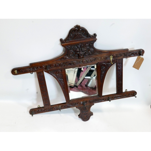 147 - A late 19th century Arts and Crafts oak wall mirror with coat hooks, carved with Green Man and scrol...