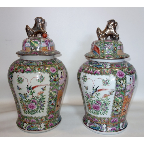 132 - A pair of 20th century Chinese famille rose temple jars and covers, with Dog of Fo finial, decorated...