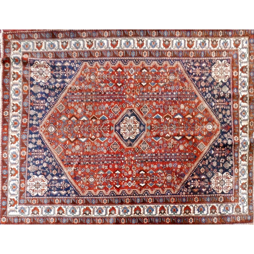 90 - A 20th century Qashqai rug having geometric motifs within diamond medallion, on a blue and rouge gro...