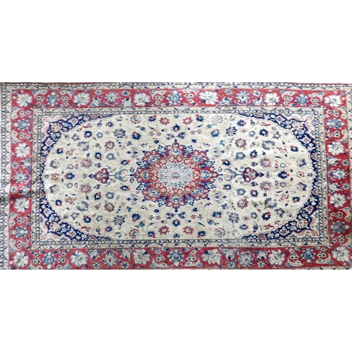 98 - A 20th century Isfahan carpet with central floral medallion surrounded by floral motifs, on a beige ...