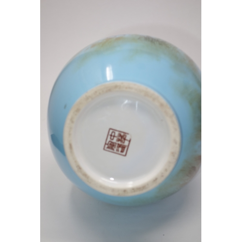 303 - A Chinese light blue glazed vase, decorated with mountainous landscape, bearing character marks to b...
