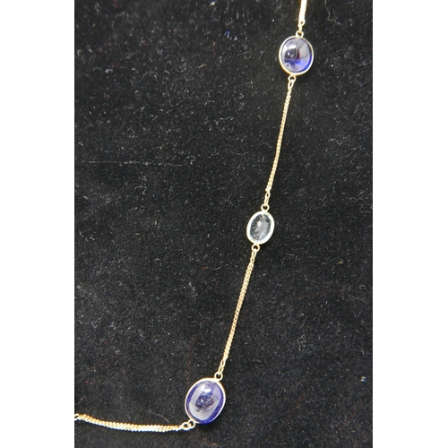 41 - A 14ct yellow gold cabochon sapphire and facated aquamarine long chain necklace composed of 8 sapphi...