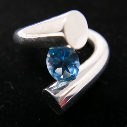 59 - A sterling silver contemporary cross-over ring centrally set with a faceted oval blue topaz, Size: P...