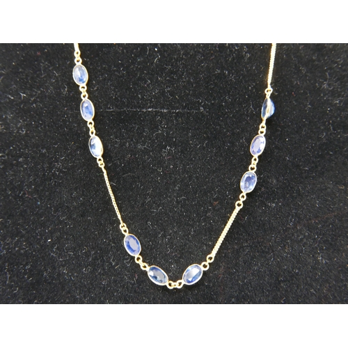53 - A 14ct yellow gold chain necklace set with 33 faceted oval natural sapphires, L: 60cm, 6.7g