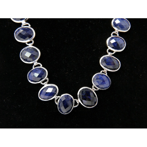 77 - A sterling silver, graduated, faceted sapphire necklace set with a total of 31 oval sapphires, L: 55...