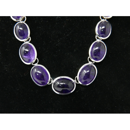 89 - A sterling silver and graduated amethyst cabochon necklace composed of 21 polished amethysts, L: 45c...