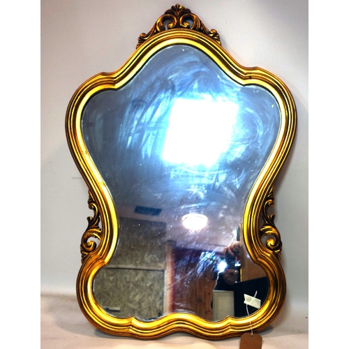 126 - A 20th century gilt mirror of cartouche form, with scrolling foliate finial, 102 x 72cm...