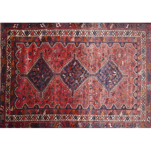 102 - A North West Persian Afshar rug the triple pole medallion with repeating petal motifs, on terracotta...