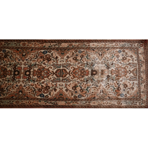 106 - A Central Persian Qum runner with repeating stylised petal and floral motifs, on an ivory field, con...
