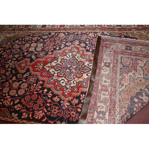 112 - A north west Persian Sarouk rug the central double pendant medallion within repeating petal motifs, ...