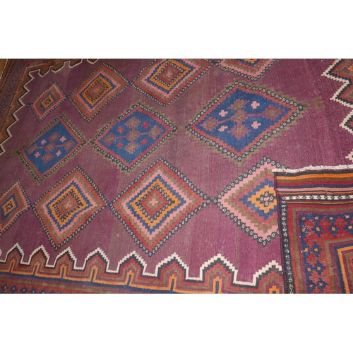 114 - A South West Persian Qashqai kelim carpet with repeating stylized geometrical motifs, on a brown fie...