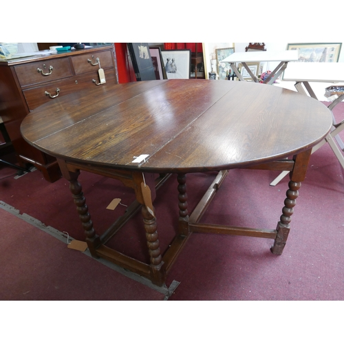 145 - An early 20th century oak drop leaf dining table...