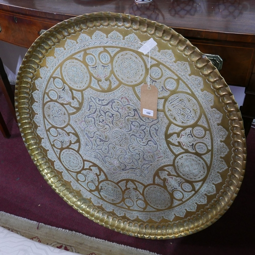 169 - An Middle Eastern brass tray top table, the top with white metal inlay, decorated with geometric sha...