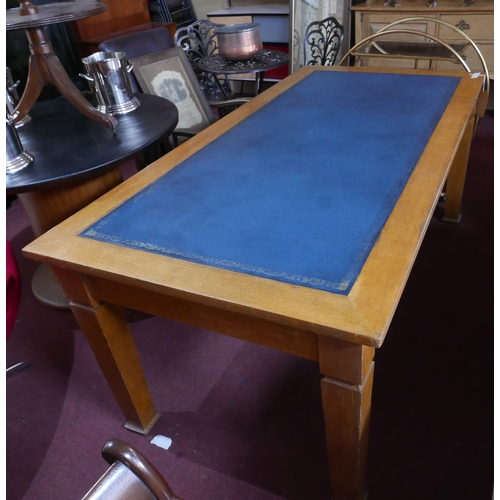 394 - A 1930's light oak library table, with leather inset top, raised on tapered legs and spade feet, H.7...