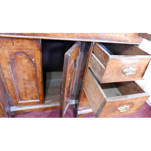 421 - An early 18th century walnut bureau bookcase, the two arched mirrored doors enclosing drawers and sh...
