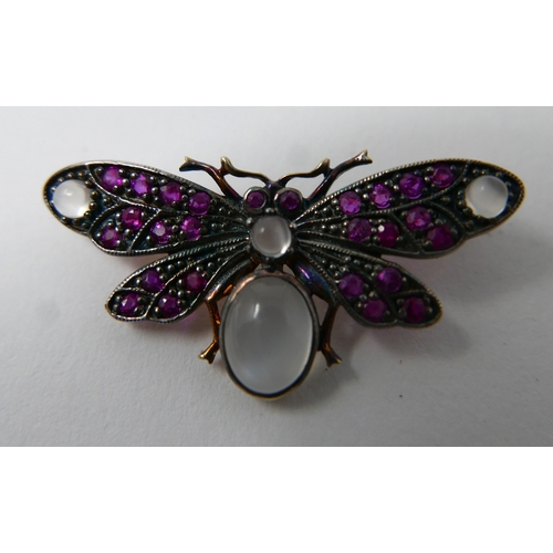 12 - A yellow gold butterfly brooch studded with rubies and four moonstone cabochons, 1.5 x 3.5cm, 3.4g...