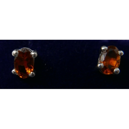 45 - A boxed pair of sterling silver and oval faceted orange tourmaline stud earrings, 5 x 4mm, 1.2g...