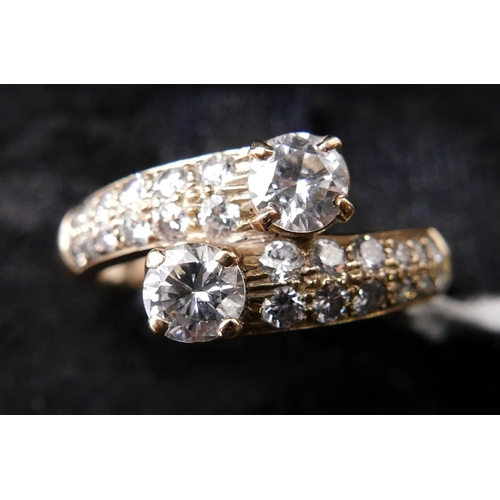 38 - A boxed 18ct yellow gold and brilliant-cut diamond cross-over ring set with 2 round brilliant cut di...