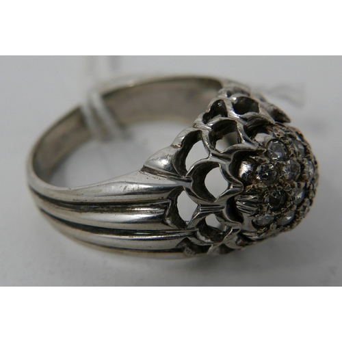 44 - A solid 18ct white gold and diamond cluster ring to a pierced outer mount and wide, ribbed shoulders...