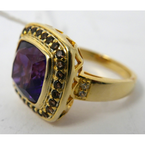 97 - A silver-gilt natural amethyst ring, centrally set with a large cushion-cut amethyst framed by an ou...