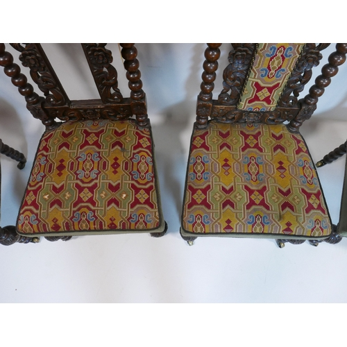 221 - A set of four Victorian oak chairs with bobbin supports and tapestry upholstery, raised on castors...