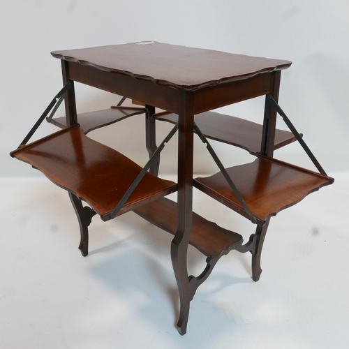 225 - An Art Nouveau mahogany lamp table with folding shelves and walnut cross banding...
