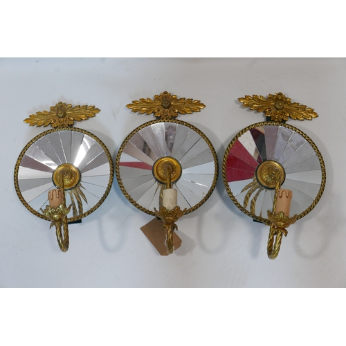 69 - A set of three Empire style gilt metal wall lights with mirrored backs, H.45 W.26cm...