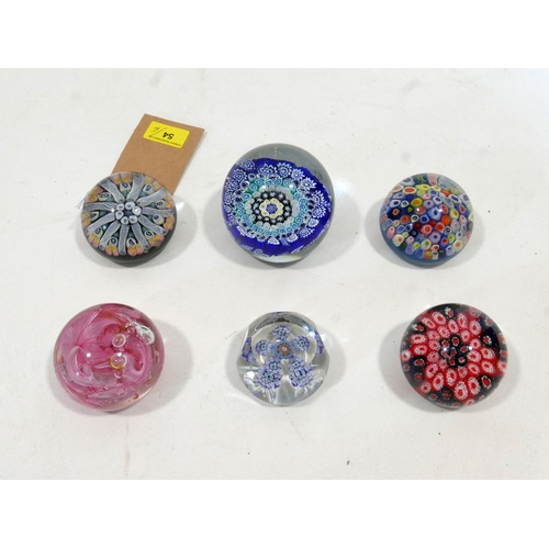 54 - A collection of six glass paperweights, to include a Strathearn example with millefiori decoration, ...