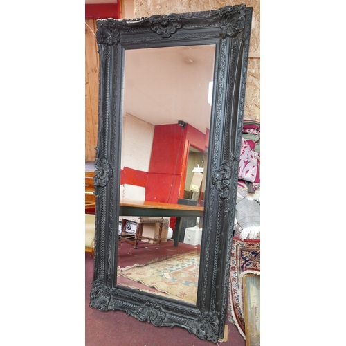281 - A large 18th century style black painted mirror with bevelled plate, 206 x 98cm...
