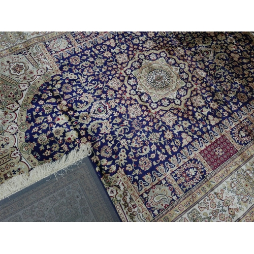 301 - A Kashan style carpet with central floral medallion, on a blue ground, contained by floral borders, ...