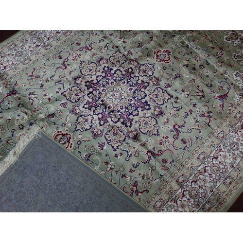 303 - A Kashan style carpet with central floral medallion, on a green ground, contained by floral borders,...