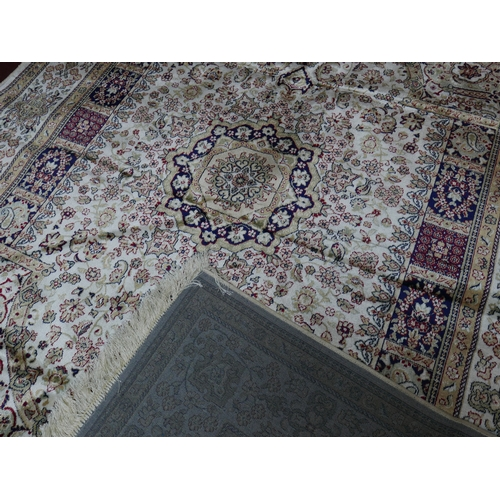 309 - A Kashan style carpet with central floral medallion, on a beige ground, contained by floral borders,...