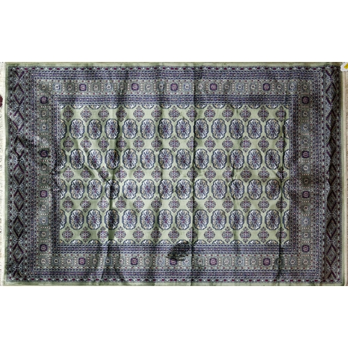 311 - A Bokhara style rug with repeating elephant pad motifs, on a green ground, conatined by geometric bo...
