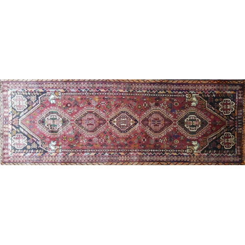 66 - A South West Persian Qashqai runner, repeating stylised pole medallion on a terracotta field with co...