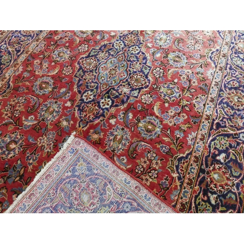 70 - A Central Persian Kashan carpet, double pendent medallion with repeating petal motifs on a rouge fie...