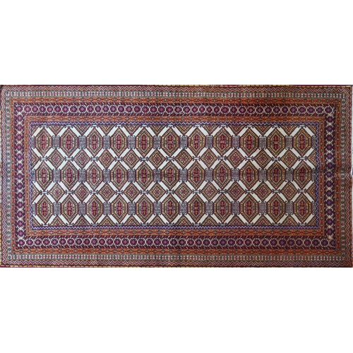 82 - A North East Persian Turkoman rug, repeating Tekkeh motifs on an ivory field within stylised geometr...