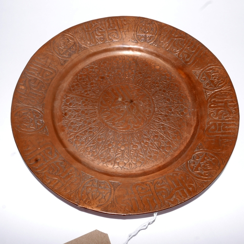 308 - A Persian copper Qajar dish, decorated with stylised flowers and Arabic inscriptions, Diameter 31cm...