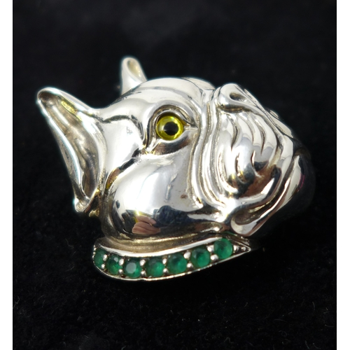 96 - A sterling silver pendant/brooch in the form of a dogs head and having an emerald studded collar...