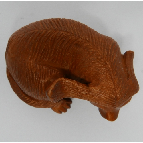 27 - A Japanese carved wooden netsuke in the form of a seated dog...
