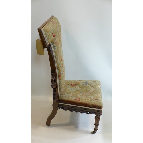 219 - A 19th century rosewood prie dieu, with floral carving, raised on floral carved legs and castors, fl...