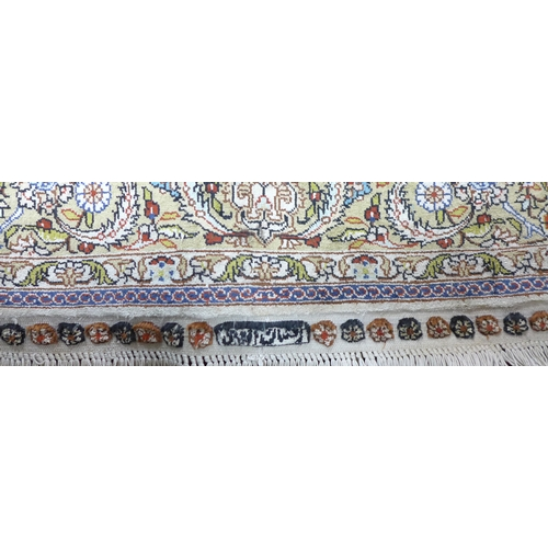 94 - A mid 20th century Turkish silk Hereke rug, signed, with floral medallion surrounded by floral motif...