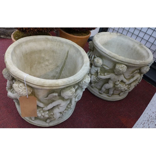 120 - Two reconstituted stone planters, decorated with a continuous procession of cherubs and floral swags...