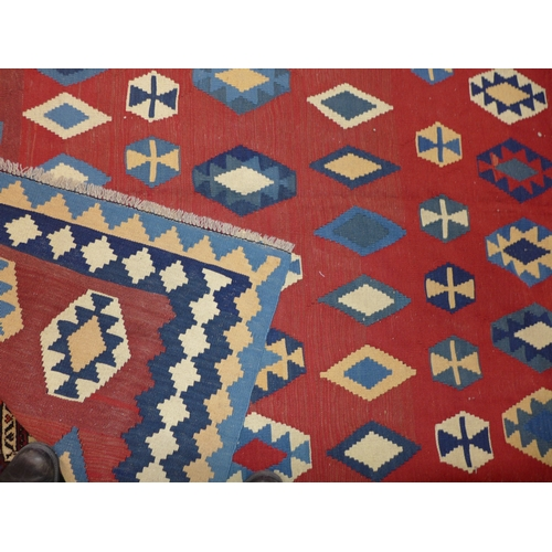 76 - A South West Persian Qashqai kelim, repeating stylised geometric motifs on a rouge field, within sty...