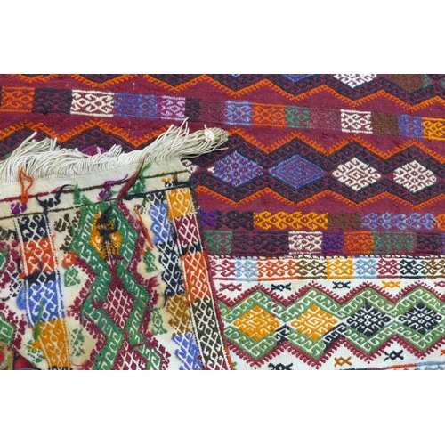 86 - A multi-coloured woven rug with all-over geometric designs and motifs within three central stripes, ...