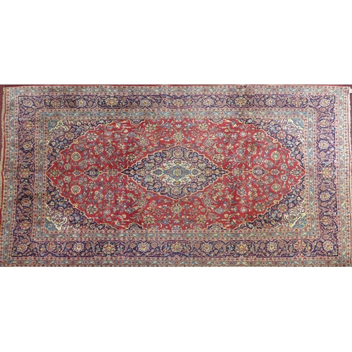 68 - A Central Persian Kashan carpet, double pendent medallion with repeating spandrels on a rouge field,...