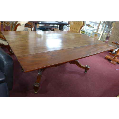 412 - A William IV mahogany drop leaf dining table, with twin pillar supports, joined by stretcher, raised...