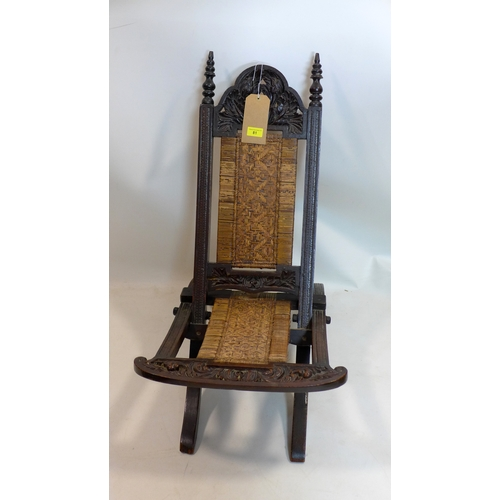 81 - A 19th century Anglo-Indian carved oak folding chair...