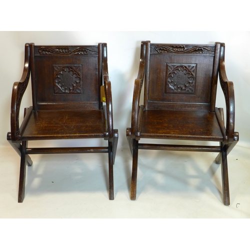 83 - A pair of 19th century oak Glastonbury chairs with carved panels...