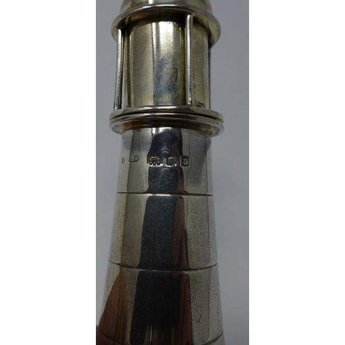 44 - An early 20th century silver lighter in the form of a lighthouse, raised on alabaster base...