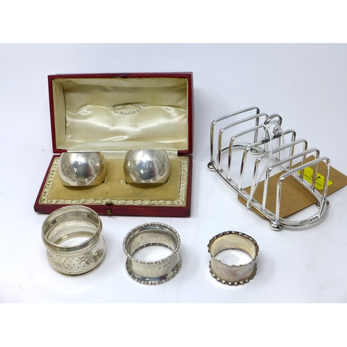 25 - An early 20th century silver toast rack together with four silver napkin rings, 9oz, and one other w...